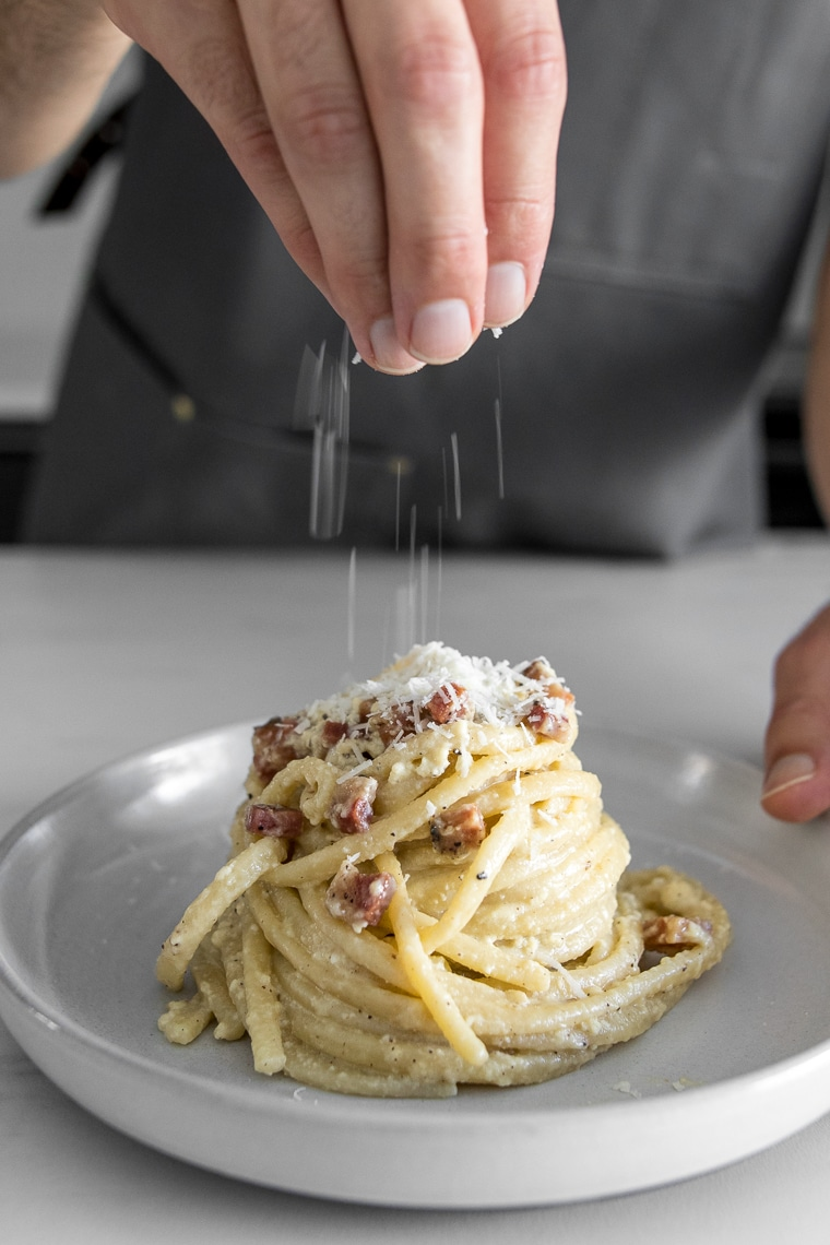Sprinkling cheese onto a plate of carbonara