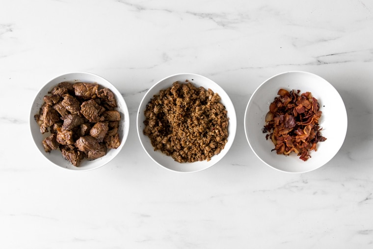 Three bowls of browned meat, beef cubes, sausage and bacon