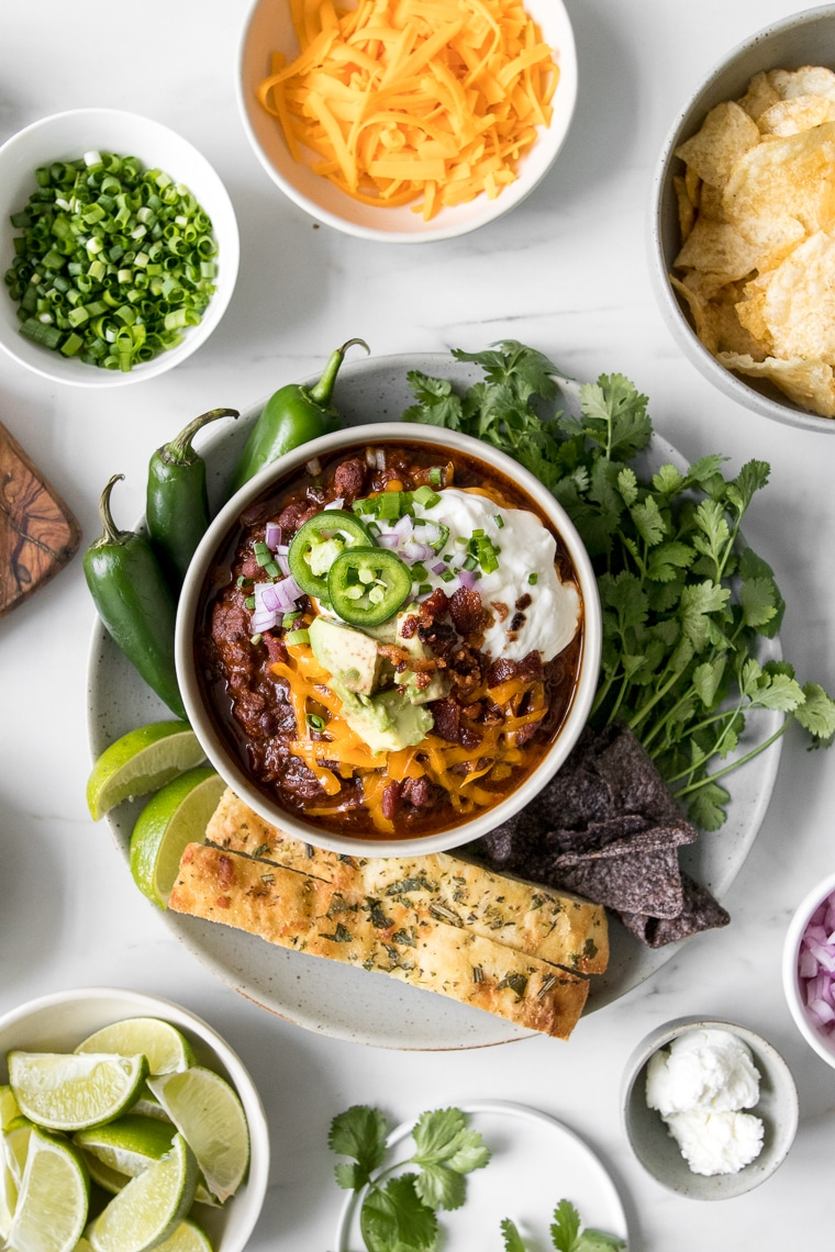 Homemade chili in a bowl topped with cheese, sour cream, avocado, and jalapeno peppers surrounded by bowl of various chili toppings