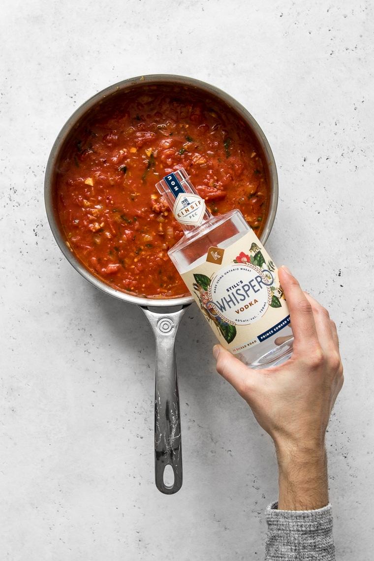 Pouring vodka into tomato sauce
