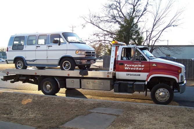 A towing truck carrying a white van