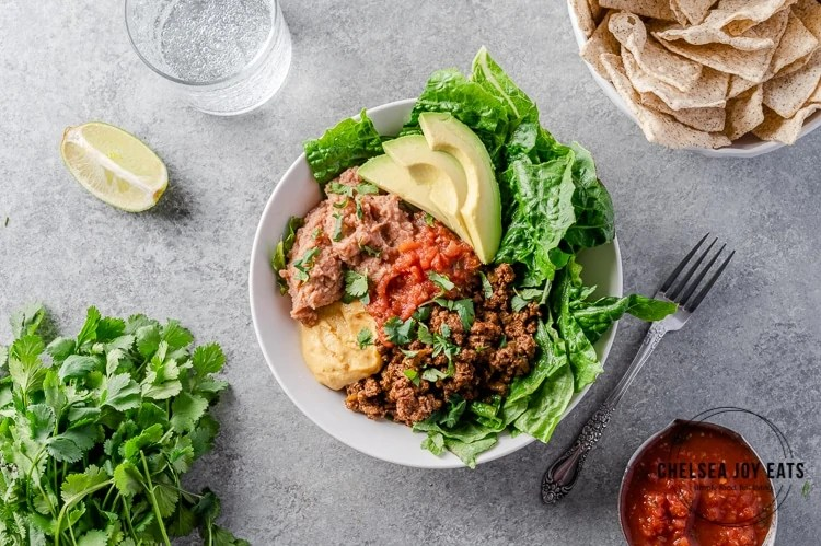 Bowl with taco meat, lettuce, beans, avocado, and nacho cheese sauce