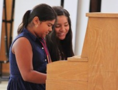 students playing piano at multicultural music camp