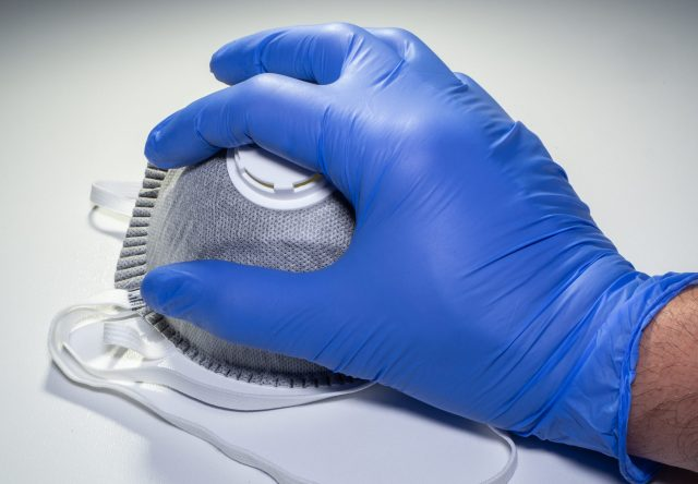 A gloved hand takes a mask from a set of FFP2 medical masks. Face mask protection against pollution, virus, flu and coronavirus. Health care and surgical concept