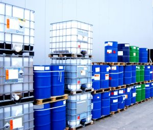 Hazardous materials White container and blue drums on an industrial storage site