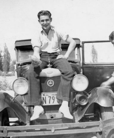 Young man on car hood