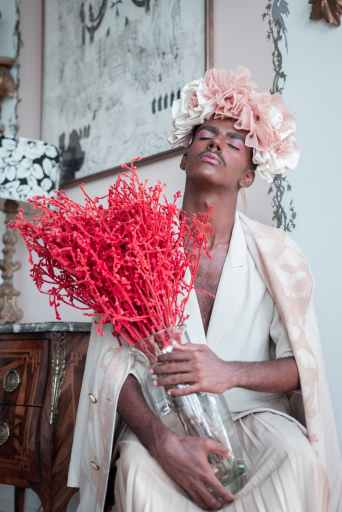 This man is wearing make-up, a floral headdress, and holding a bouquet, but is he queer? We don't know.