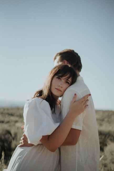 An opposite-sex couple dressed in white hug under a clear blue sky. They may look heteronormative, but we can't know if either of them has affinity with bi/pansexuality.