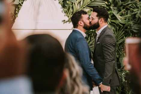 Two bearded men wearing suits kiss in front of an out-of-focus crowd.