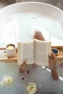 An overhead shot of a spa bathtub shows a person's hands holding a book above the water. A snack tray is across the tub, and flowers float in the water.