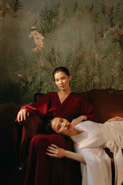 Two Asian women dressed in flowing robes rest on an ornate sofa. The woman to the right of the frame, who wears white, rests her head in the other woman's lap.