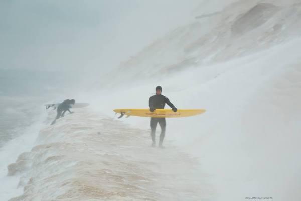 Surfers climbing over ice on Lake Michigan