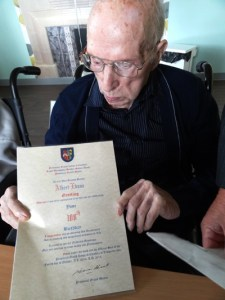 Albert Evans examines 100th Birthday Certificate signed by RWPGM