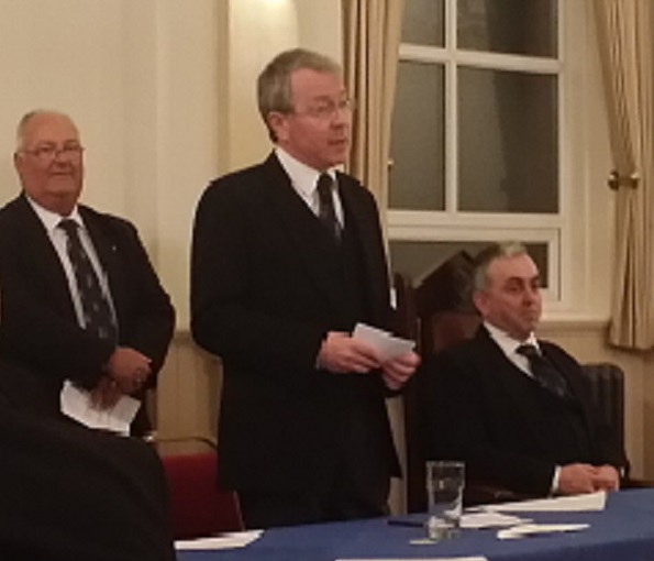 APGM Paul Massie address the Festive Board at St. Hilary Lodge. WM Paul Rowbottom seated, DC Graham Roberts in the background ensuring everything runs smoothly