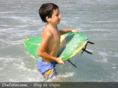 Niño surfer en la playa de Lopes Mendes
