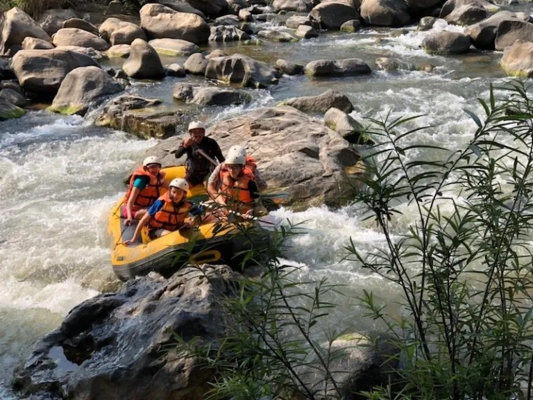 Tourists whitewater rafting