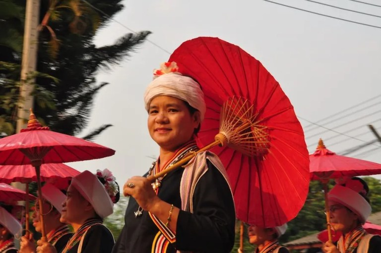 Woman in traditional dress with umbrella Tai Lue people