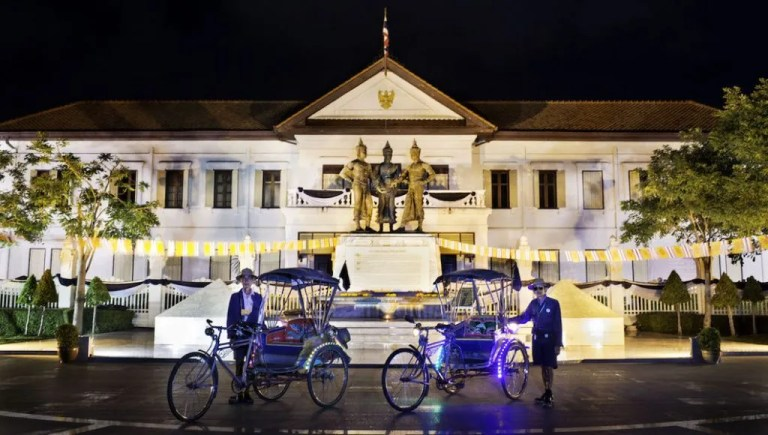 Bicycle taxis in front of colonial style building