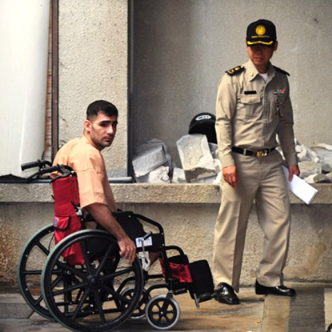 Iranian Saeid Moradi, who had his legs blown off as he hurled a bomb while fleeing Thai police in February 2012, arrives at Bangkok South Criminal Court on Tuesday