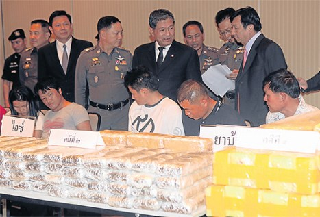 Drug suspects are brought to the Royal Thai Police Office yesterday as Deputy Prime Minister Chalerm Yubamrung and police chief Adul Saengsingkaew discuss three major drug raids in the past few days. More than 2.2 million methamphetamine tablets and 47kg of crystal meth were seized in the busts