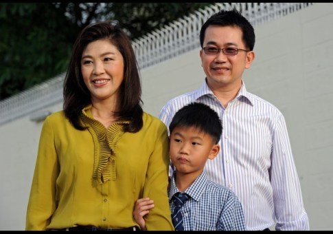 Yingluck Shinawatra (L), candidate for the Pheu Thai party ahead of the July 3 general election and sister of former premier Thaksin Shinawatra, poses for a photo with her husband Anusorn Amornchat (R) and their son Supasek