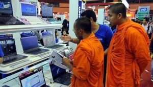Thai buddhist monks looking at discounted notebooks displayed at the Commart Thailand in Bangkok.