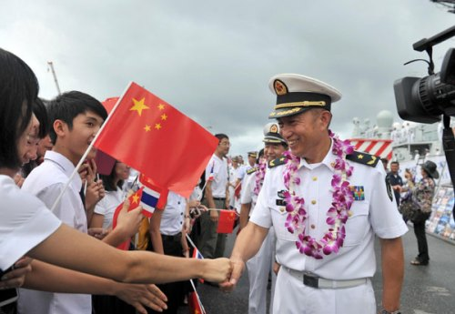 Yuan Yubai (R), commander of the Chinese flotilla, shakes hand with local Chinese at Sattahip naval base in Chon Buri province of Thailand, Sept 12, 2013. On invitation from Thailand's navy, three Chinese Navy ships called at Thailand's Sattahip naval base Thursday for a five-day visit on their way back to China from an escort mission in the Gulf of Aden and the waters off Somali.