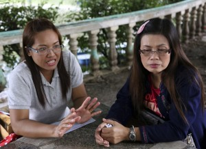Jongkon Kongthin, 36, left, wife of Yuthapoom Martnok and Yuthapoom's sister Pinyo Ruaylarp, 42, talk during an interview outside a prison in Bangkok