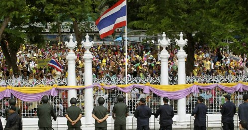 Members of the People's Alliance for Democracy or Yellow Shirts wave and chant slogans during a rally outside the heavily guarded Parliament in Bangkok, Thailand