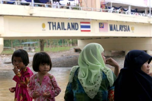 Villagers look out over the Kolok river to Malaysia during the opening of the second Thai-Malaysian Friendship bridge, which connects Narathiwat and Malaysia's Kalantan state. (Bangkok Post file photo)