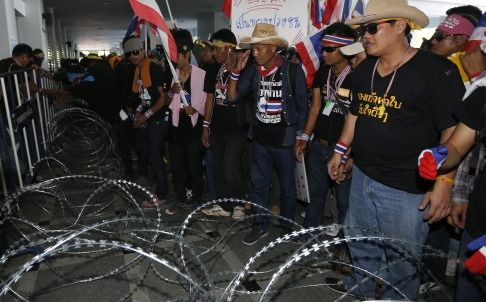 Thai anti-government protesters behind razor wire at the Department of Special Investigation in Bangkok