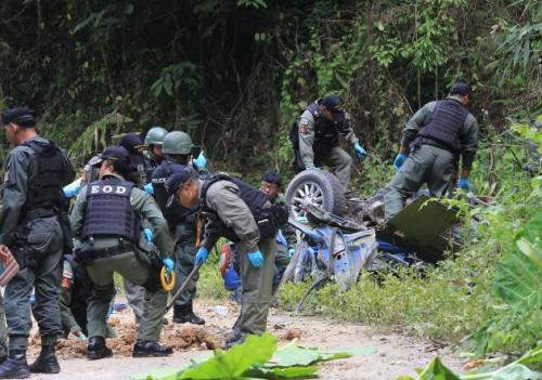 Bomb-disposal officials inspect an overturned armoured vehicle on a road in Yala. The vehicle was targeted in a bomb attack. One policeman was killed and four others injured.