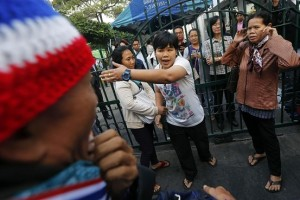A voter, center, reacts as antigovernment protesters stopped her from entering a polling station they blocked in central Bangkok on Sunday.
