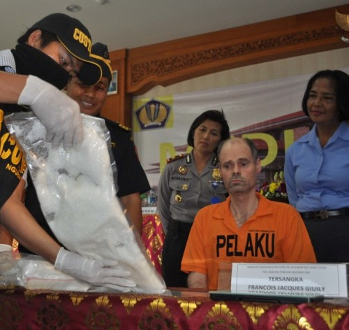 French national Francois Jacques Giuily, wearing orange shirt, is arrested after allegedly attempting to smuggle 3 kg of crystal meth via Bali's Ngurah Rai Airport.