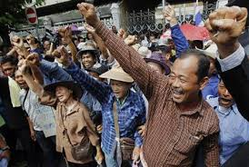 Rice farmers shout slogans during a protest outside the Government House