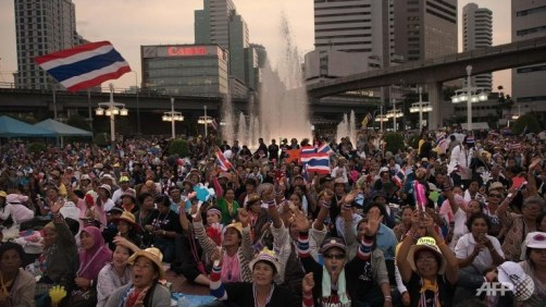 Thai anti-government protesters wave national flags at Silom intersection during ongoing rallies in Bangkok