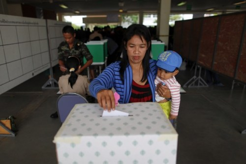 A woman holds her baby as she casts her ballot