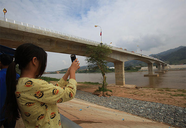 A visitor takes a photo at the fourth Thai-Lao Friendship bridge, which opened four months ago. It links Chiang Rai's Chiang Khong district in northern Thailand with Ban Houysay in Laos and is expected to boost tourism.TAWATCHAI KEMGUMNERD