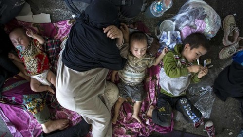 Uighur refugees rest inside a temporary shelter after they were detained at the immigration regional headquarters near Thailand-Malaysia border in Hatyai
