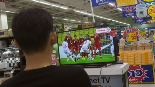 A Thai shopper watches a soccer match on a flat-panel television at a shopping mall in Bangkok, Thailand Wednesday, June 11, 2014. (AP / Sakchai Lalit)