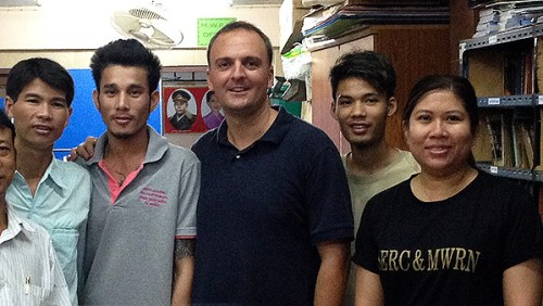 Labor rights activist Andy Hall, center, with members of the Migrant Worker Rights Network. Pic: AP.
