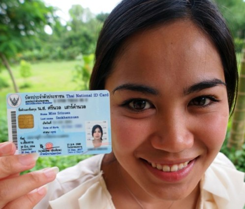 "Srinuan ""Aor"" Saokhamnuan, who was born stateless in Thailand, holds up her new Thai identification card after authorities granted her citizenship"