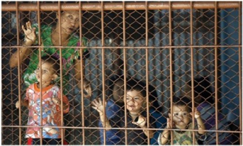 AFP picture of some children of Burma standing behind bars with other detainees in a crowded detention cell in Mae Sot, Thailand