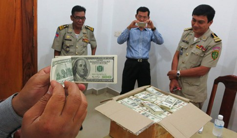 Police and court officials examine notes from a seized haul of $7.16 million in counterfeit hundred-dollar bills in Battambang, Cambodia Sept 30. Cambodian police seized the fake notes on Sept 19 near the border with Thailand, the largest seizure of fake US notes in Southeast Asia for about a decade and the biggest-ever in Cambodia. (Reuters photo)