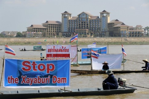 Thai activists and villagers who are affected by the controversial Xayaburi dam protesting with banners while navigating on the Mekong river, with Laos territory in the background,