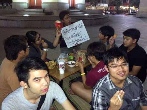 Bangkok students participate in a short-lived picnic at Democracy Monument Wednesday night organised in support of detained student activists in the Northeast. Police quickly shut down the activity, deeming it an anti-coup protest.