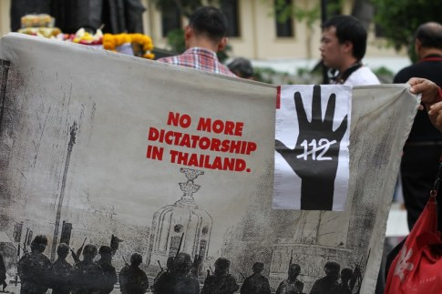 Protesters hold up a banner demanding a reform in Article 112 or the Lese Majeste