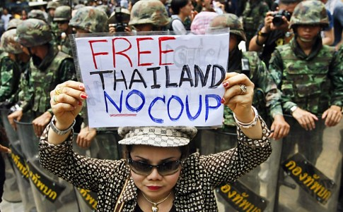 A Thai demonstrator holds a placard during a demonstration against the military coup at a shopping district in central Bangkok. Photo: EPA