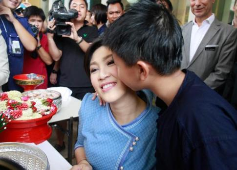 Yingluck Shinawatra gets a kiss from her son while celebrating the Thai New Year