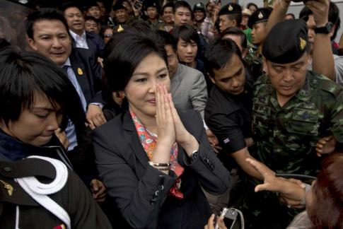 Ousted Thai prime minister Yingluck Shinawatra gives a traditional greeting to supporters in a suburb of Bangkok